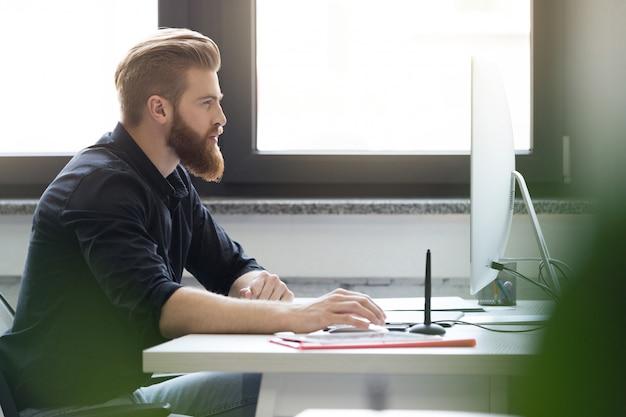 彼の机に座っている若いひげを生やした男の側面図