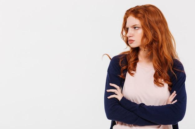 腕を組んで怒っているかなり若い赤毛の女性