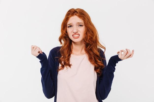 孤立した立っている混乱の若い赤毛の女性