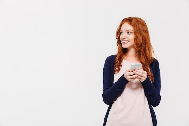 幸せな美しい若い赤毛の女性が携帯電話でチャットします。