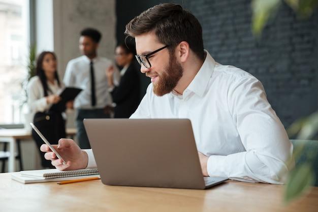 陽気な若い白人実業家が携帯電話でチャットします。
