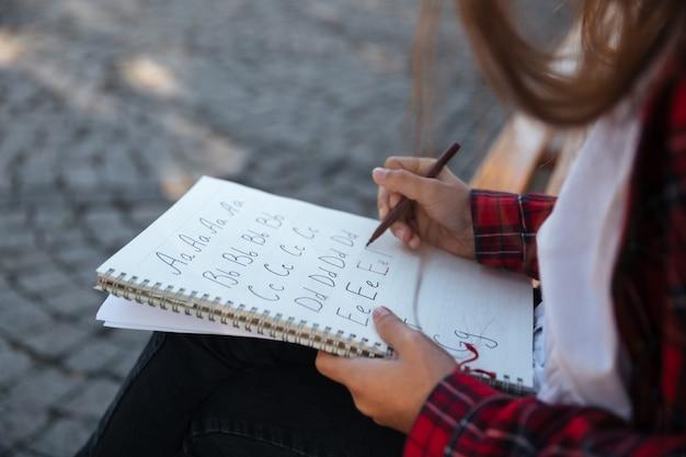 Обрезанный вид сбоку школьницы, сидя на открытом воздухе