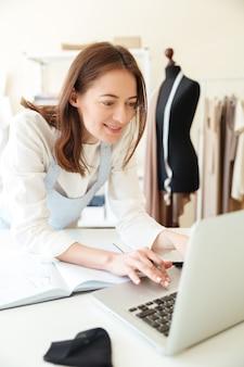 Улыбается женщина швея в работе с ноутбуком и ткани в мастерской