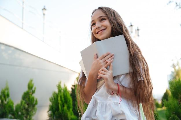 本を持って笑顔の若い女の子の下からの眺め
