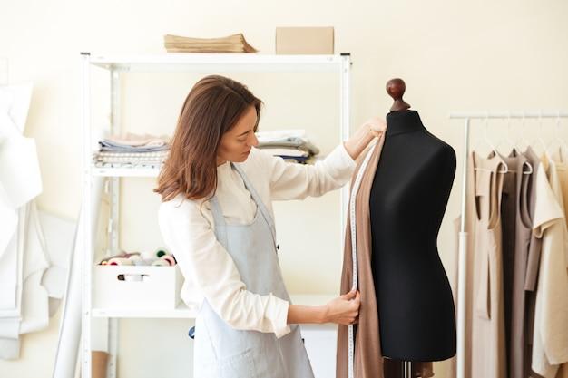 Брюнетка-швея в фартуке меряет красивую ткань на черном манекене в мастерской