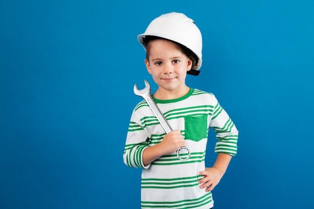 Веселый мальчик в защитном шлеме позирует с помощью гаечного ключа