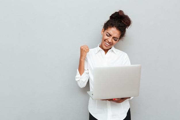 陽気なビジネスの女性は、勝者のジェスチャーを作ります。