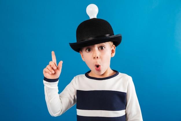 Шокирован молодой мальчик в шляпе с лампочкой, имея идею