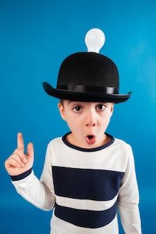 Вертикальное изображение потрясенного мальчика в шляпе с лампочкой