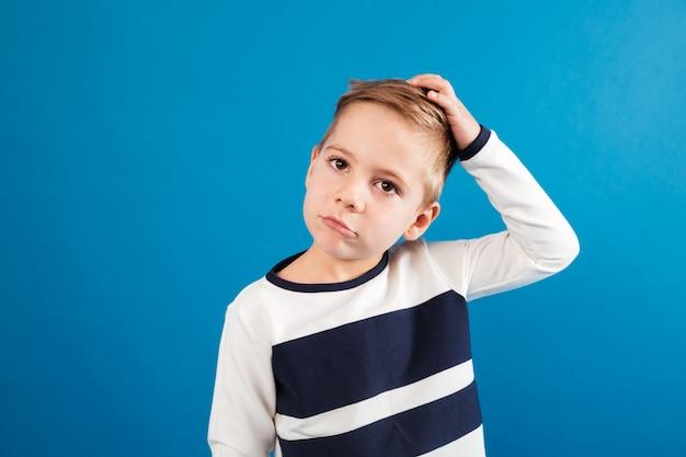 Задумчивый молодой мальчик в свитере касаясь его голове