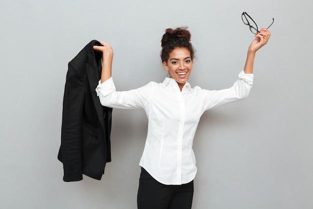 探している灰色の壁の上のアフリカの笑みを浮かべてビジネス女性。