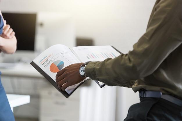 Афро американец укомплектовывает личным составом руки, держа документ в офисе