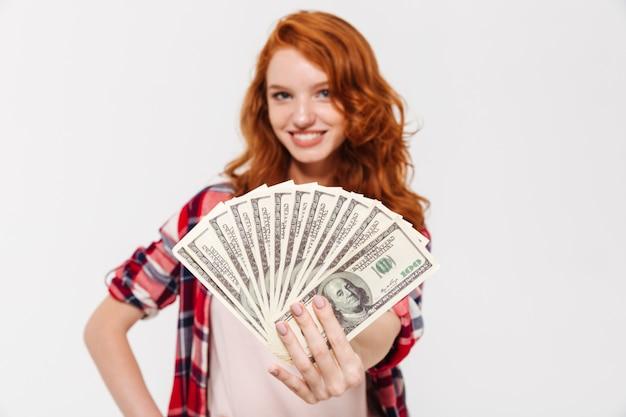 陽気なかなり若い赤毛の女性がお金を保持しています。