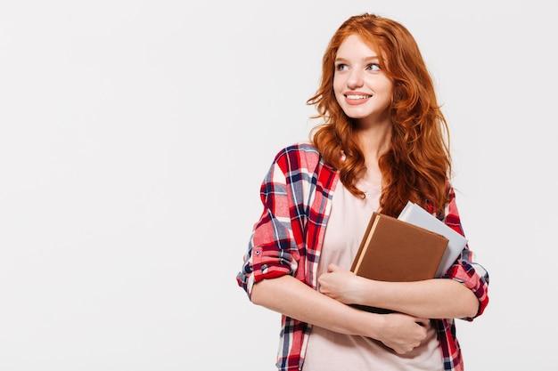 Довольная рыжая женщина в рубашке держит книги и смотрит в сторону