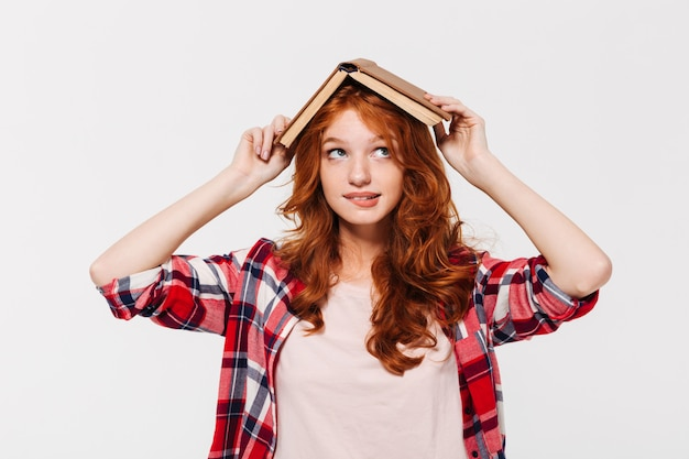 Задумчивая рыжая женщина в рубашке держит книгу на голове