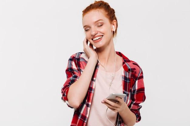 Довольная рыжая женщина в рубашке и наушниках слушает музыку