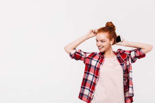 Улыбающаяся рыжая женщина в рубашке и наушниках слушает музыку