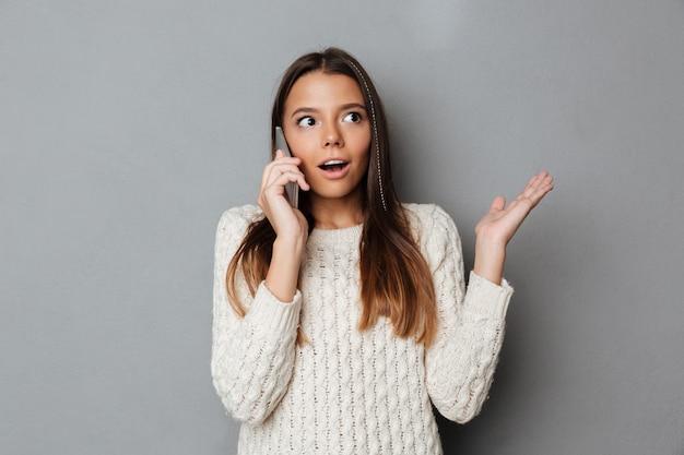 Портрет удивленной потрясенной девушки в свитере