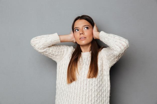 Портрет молодой обеспокоенной девушки в свитере