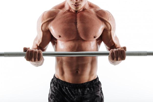バーベルを行使して黒のショートパンツで筋肉の汗をかいたスポーツ男の写真をトリミング