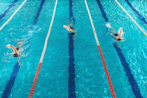 Три мужчины пловцы мчатся друг против друга