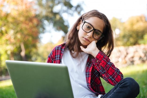 Уставшая брюнетка школьница в очках сидит на траве