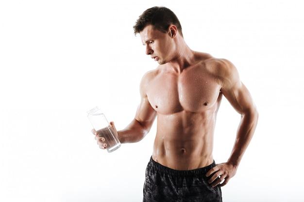 集中して若いスポーツマン飲料水