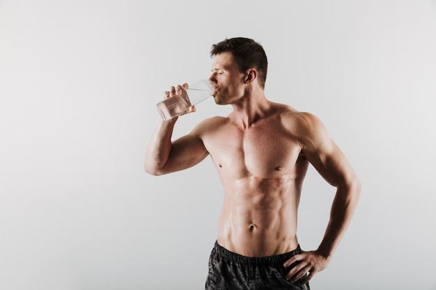 強い深刻な若いスポーツマン飲料水