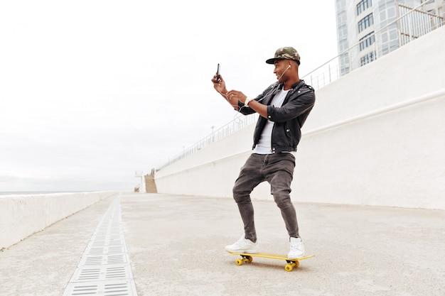 Молодой африканский человек используя телефон и слушая музыку.