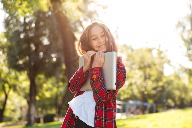 Счастливая маленькая девочка стоя в парке пока обнимающ ее компьтер-книжку