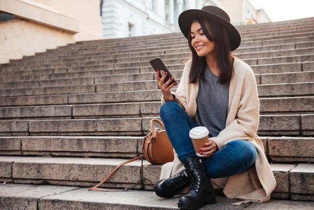 Портрет привлекательной улыбающейся женщины с помощью мобильного телефона