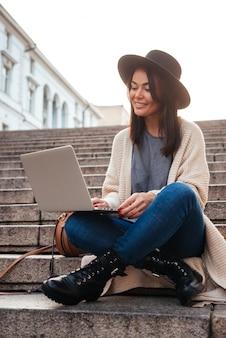 Портрет счастливой красивой женщины, используя портативный компьютер
