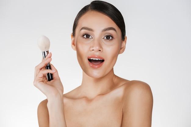 カメラで見ていると、白で分離された化粧ブラシを保持している完璧な肌とゴージャスな女性の美しさの写真