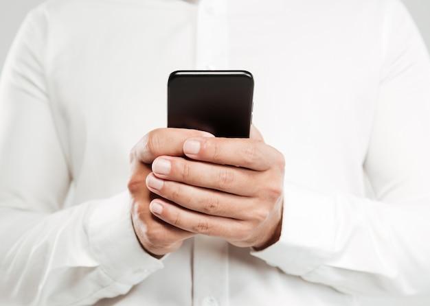 Обрезанное изображение молодого человека в чате по телефону.