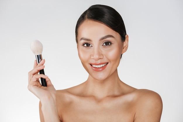 カメラで見ていると白で分離された化粧ブラシを保持している完璧な肌と満足の笑みを浮かべて少女の美しさの写真
