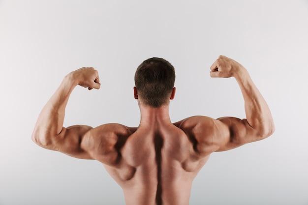 スポーツマン立って示す上腕二頭筋。