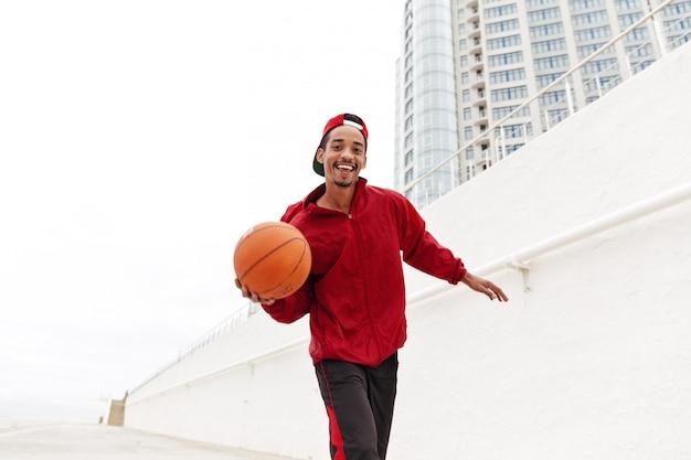 歩いて幸せな若いアフリカ人はバスケットボールをプレーします。