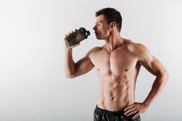 深刻な若いスポーツマン飲料水