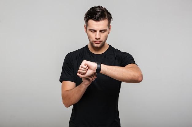 Портрет сфокусированного молодого спортсмена регулируя его наручные часы