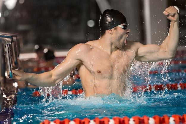 Счастливый мужской пловец держит стартовый блок