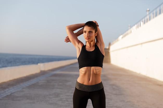 Молодая серьезная здоровая женщина протягивая и тренируя в утре