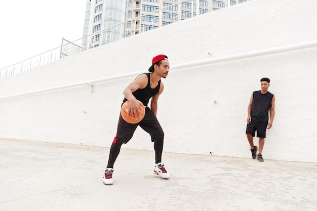 Концентрированные молодые африканские спортивные мужчины играют в баскетбол