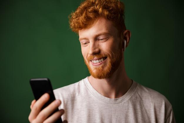 Крупным планом молодой веселый кудрявый рыжий бородатый молодой человек, слушая музыку с аэродромами