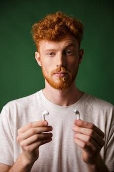 彼のエアポッドを示す上げられた眉毛と赤毛の巻き毛の男のクローズアップの肖像画、
