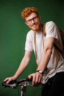 バックパックとレトロなカメラ、自転車に乗る準備ができて若い陽気なリードヘッドひげを生やしたヒップスター