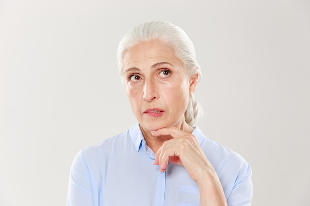 Крупным планом мышления красивая старая женщина в синей рубашке, глядя вверх