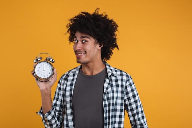 目覚まし時計を示す笑みを浮かべて幸せなアフリカ人の肖像画