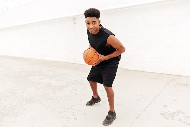Молодой африканский человек играть в баскетбол на открытом воздухе.