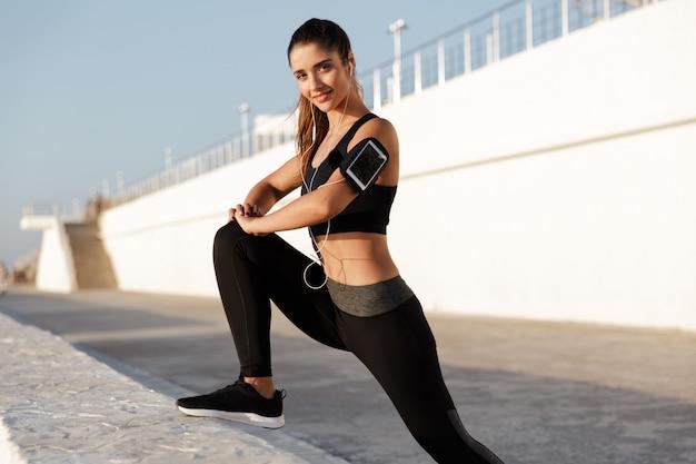 Веселая молодая спортивная женщина слушает музыку