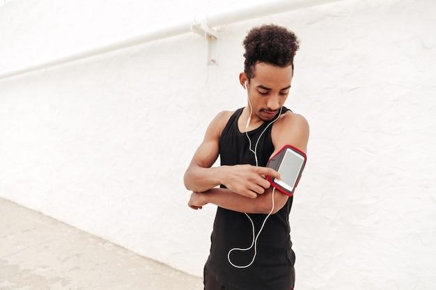 Сконцентрированная молодая африканская резвится музыка человека слушая.